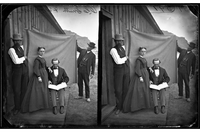 Black and white image of a man and woman posing for a picture while two men hold a sheet behind them
