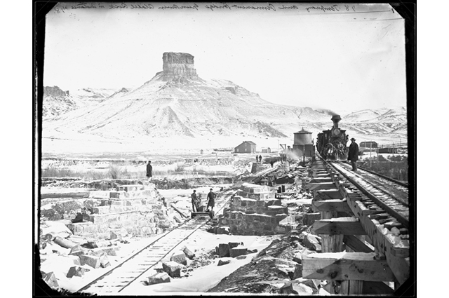 Black and white image of a railroad being built while a group of men stand on the tracks
