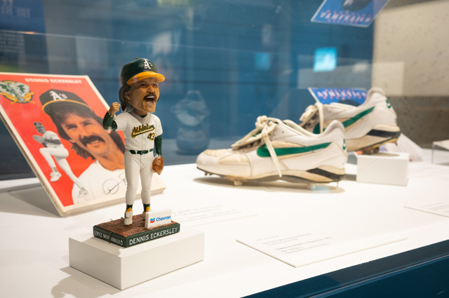 Display case with a bobblehead of Dennis Eckersley along with an old magazine with his face on the cover and a pair of cleats