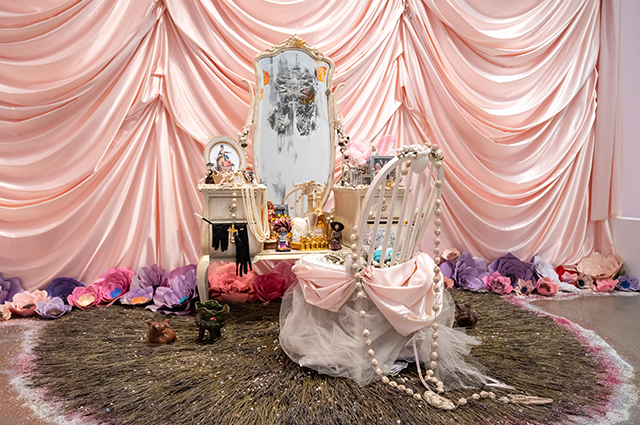 A large pink ofrenda featuring a white vanity with a large mirror, jewelry, and pink accessories