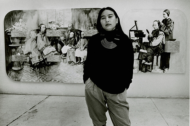 Black and white photograph of Hung Liu standing in front of a piece of her artwork.