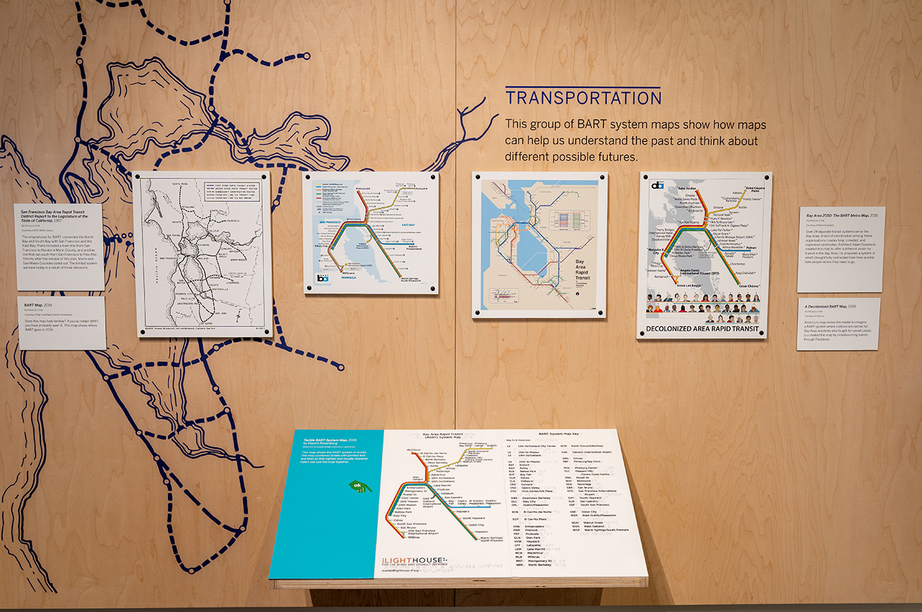 A series of artist renditions of BART maps hanging on the wall