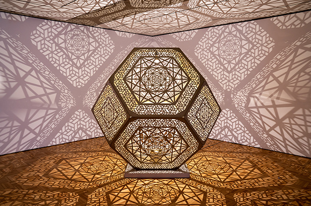 A spherical sculpture made of geometric patterns that illuminates the room around it with triangular shadows