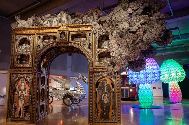 A large, intricately designed, golden paper arch takes up a large room with a silver dragon car and large colorful mushrooms in the back