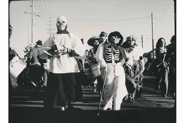 A group of people dressed as skeletons march down the street
