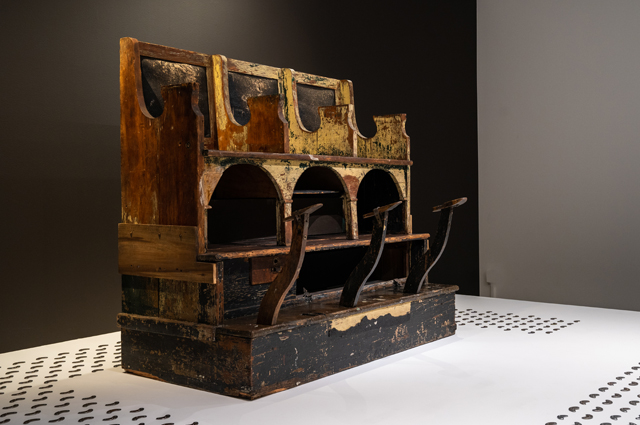 A large wooden shoe shine stand against a black background