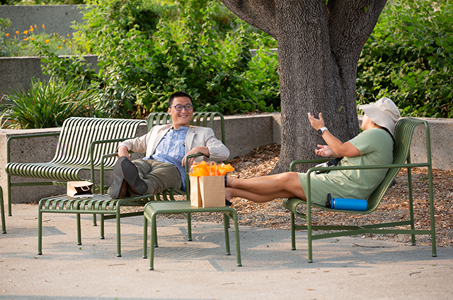 Two people converse in the OMCA gardens after picking up goods from the OMCA store.