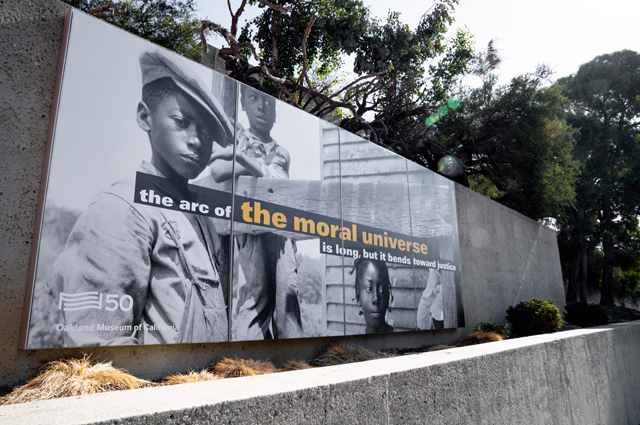 For Freedoms billboard outside of OMCA reading: the arc of the moral universe is long, but it bends toward justice