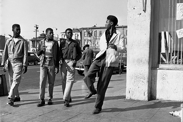 Black and white image of a group of 4 young men walking in downtown Oakland