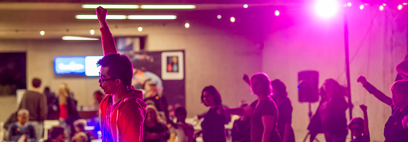 A man dances among other people at Friday Nights at OMCA