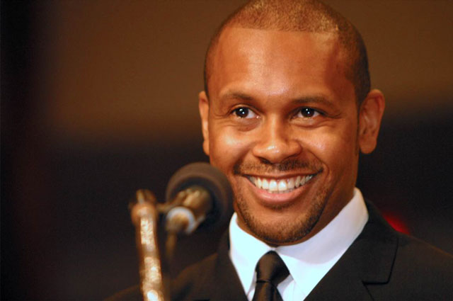 Head-on portrait of Kevin Powell smiling into a microphone.