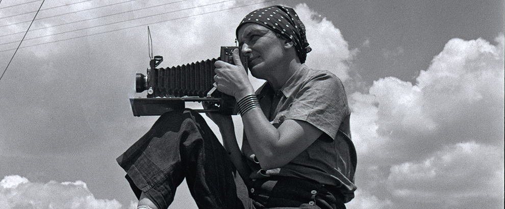 Black and white photo of Dorothea Lange sitting on top of a car with a camera