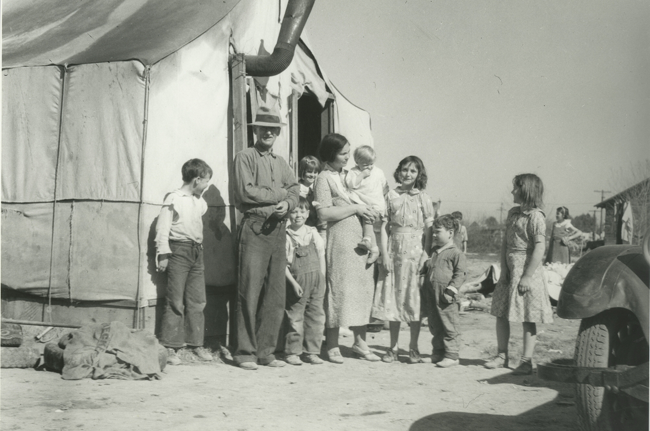 A black and white image of a family standing outside of a tent structure