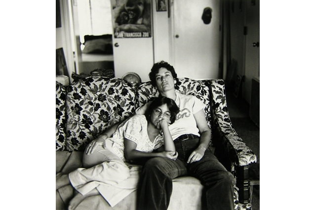 A black and white image of a mother embracing her daughter as they lounge on a couch