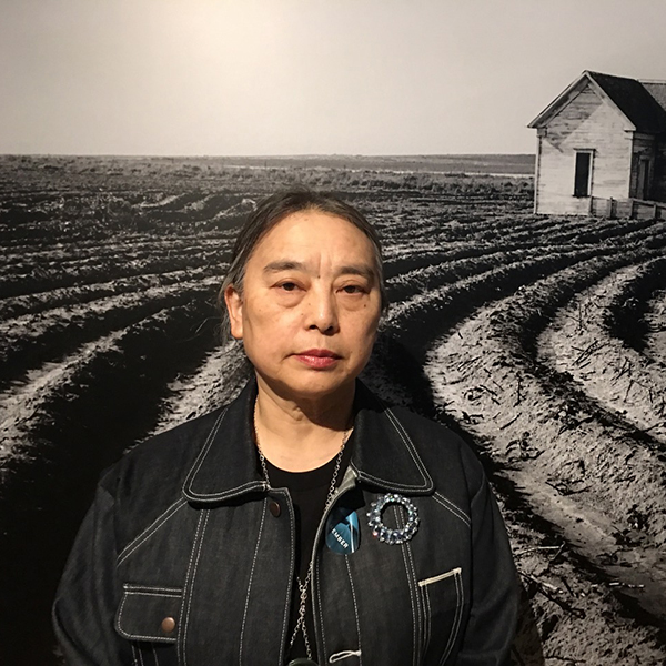 Hung Liu stands in front of a black and white Dorothea Lange photo
