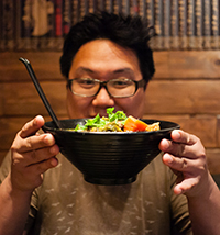 Headshot of Luke Tsai holding a bowl of food