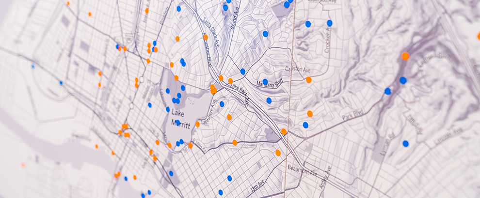 A large map of downtown Oakland with orange and blue dot stickers sprinkled around