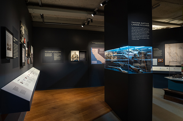OMCA's Taking Native Lands and Lives section, featuring a large glass case with several rifles in the center