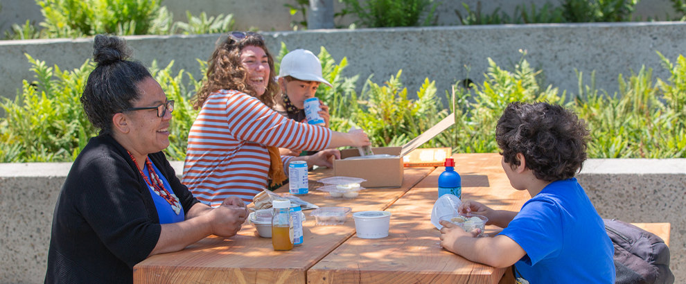 People enjoying lunch and laughing in the OMCA gardens.