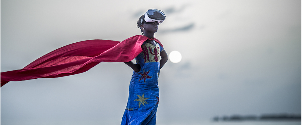 A Black child wearing a VR headset and standing in a superhero pose while a red cape flows behind them