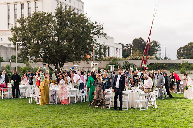 Wedding guests stand and cheer in the OMCA garden.