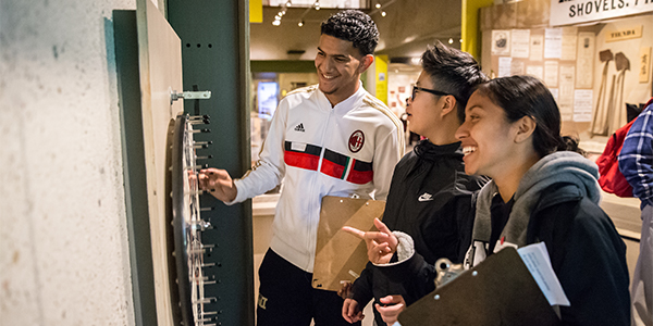 Three teenagers laugh together while exploring the Gallery of California History.