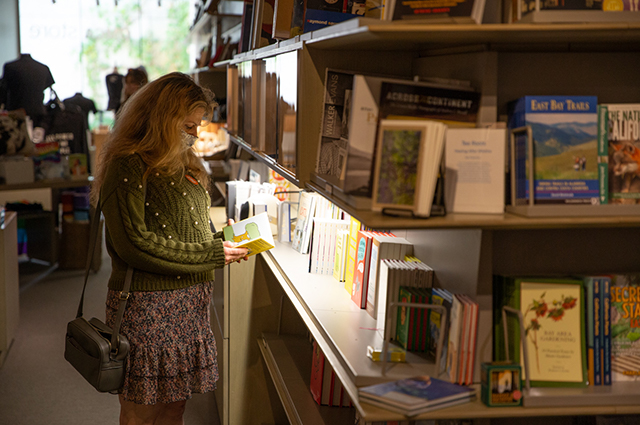 A woman reads a book in the OMCA store.
