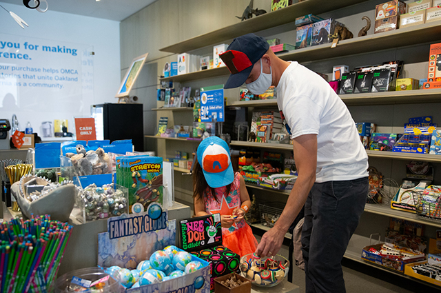 A man and child look at toys in the OMCA store.