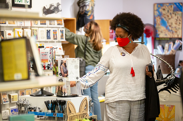 A woman wearing a red mask browses in the OMCA store.