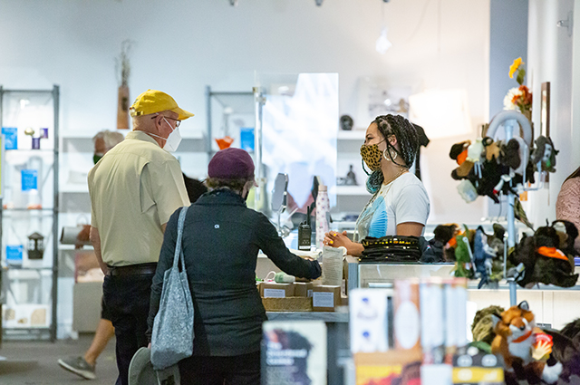 Two people purchase something at the cashier of the OMCA store.