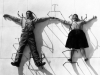 A black and white photo of Charles and Ray Eames lying on the floor underneath metal chair bases positioned above them
