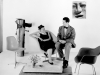 A black and white photo of Charles and Ray Eames sitting on a chaise couch and smiling at each other