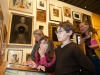 A family of two children and two adults view art in the Gallery of California Art