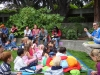 A man reads to a large group of young children and their parents in the OMCA Gardens