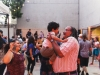 A man holds up his son as they dance in the OMCA amphitheater