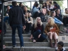 A large group of people sit on cement steps in the OMCA Amphitheater