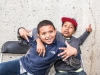 Two young boys hug and smile, posing for the camera