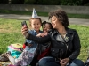 A woman takes a selfie with two smiling young girls seated in the OMCA garden