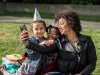 A woman with two children pose for a camera phone in the Oakland Museum of California Gardens