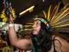 A woman dancing while wearing an Aztec feathered headdress at the Days of the Dead Community Celebration at the Oakland Museum of California