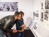 A man and daughter read text on a wall of black and white photographs