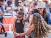 A woman dances with two girls in the OMCA amphitheater