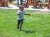 A young boy happily runs across bright green grass