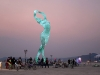 A large blue sculpture of a feminine figure in the desert of Black Rock City