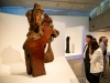 people looking at wooden jb blunk sculpture inside exhibition