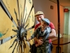 A dad holds up his young son as he spins a large wheel inside No Spectators: The Art of Burning Man