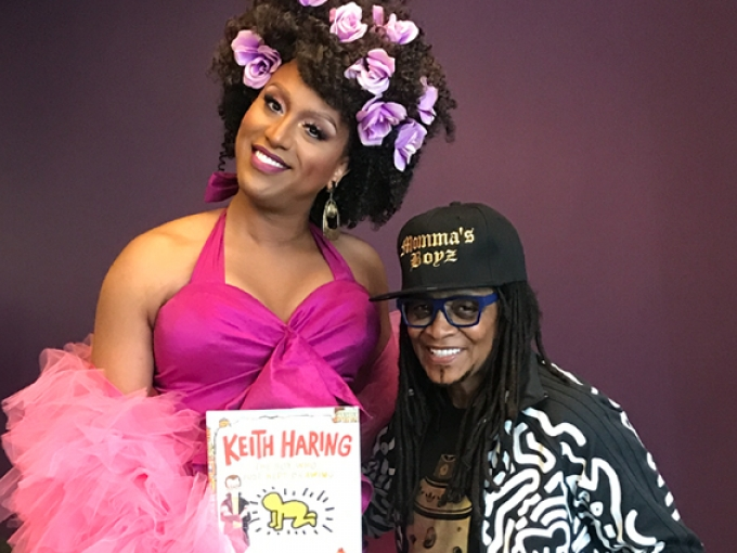 A drag queen with purple flowers in her hair holds a Keith Harring book and poses with a fan wearing a Momma's Boyz hat