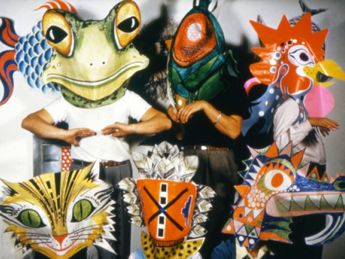 A group of Eames staff members wearing large colorful masks of animals and insects