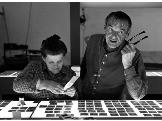 A black and white picture of Charles and Ray Eames choosing photo slides