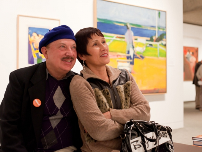 Two people look at artwork in the Gallery of California Art